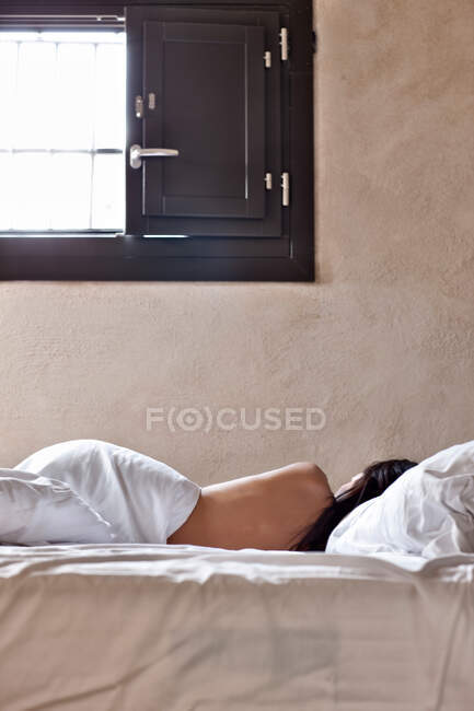 Back view of brunette topless woman sleeping in bed covered with white bed sheet on background of window with sunlight coming in — Stock Photo