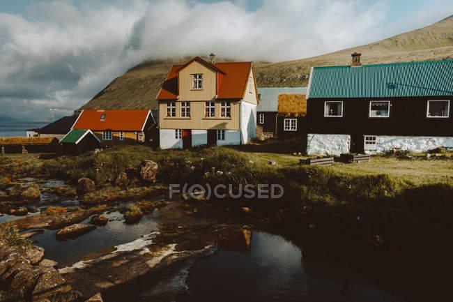 Maisons de village traditionnelles confortables sur les collines et la rivière sur l'île de Feroe — Photo de stock