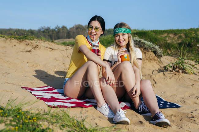 Trendige Mädchen mit Drinks am Strand — Stockfoto
