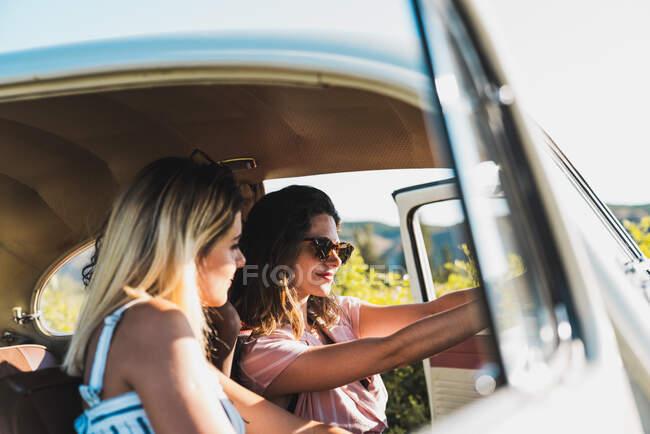 Grupo de mulheres multiétnicas felizes no carro dirigindo juntos na luz solar brilhante e rindo — Fotografia de Stock