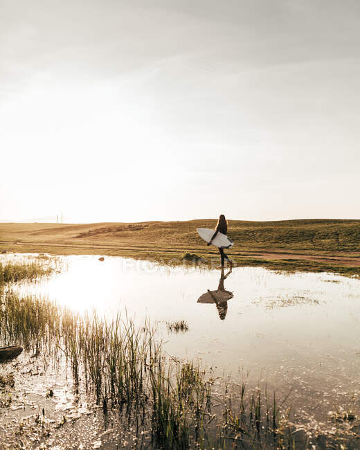 Side view of unrecognizable person carrying white surfboard while walking near pond in beautiful countryside — Stock Photo