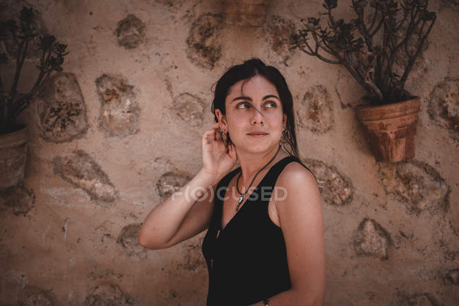 Lovely woman near wall and plant — Stock Photo