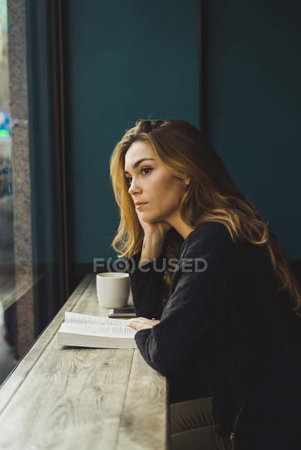 Verträumte junge Frau sitzend mit Buch und eine Tasse Kaffee im café — Stockfoto