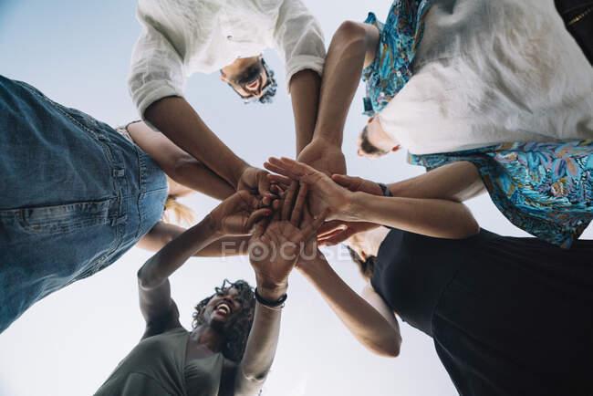 Von unten Aufnahme junger Freunde, die lachen und die Hände zusammenhalten, während sie vor dem Hintergrund des klaren Himmels stehen — Stockfoto