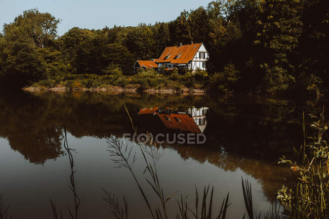 Big house with orange roof built at forest and pond on Feroe Island — Stock Photo