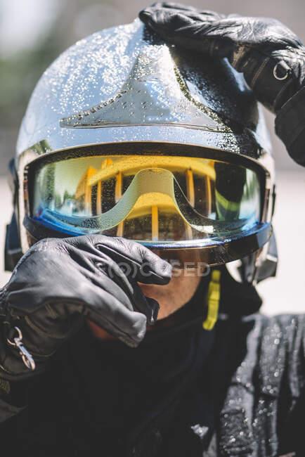 Пожарный позирует со шлемом, смотрит в камеру.. — стоковое фото