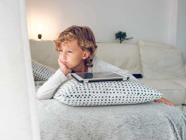 Garçon réfléchi couché avec tablette numérique sur le canapé et regardant loin — Photo de stock