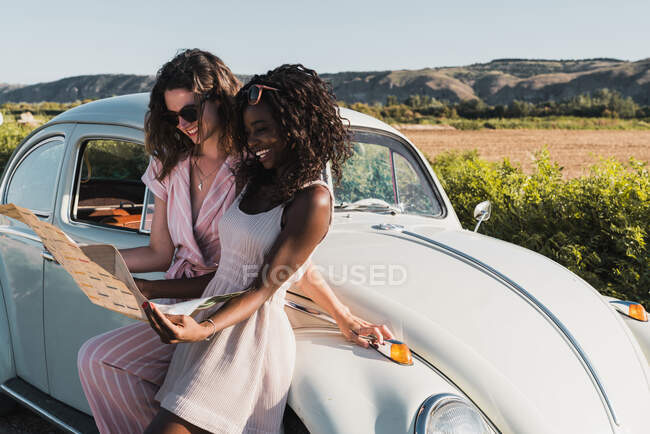 Trendy multiethnic women standing near vintage car and reading map while traveling together in summer — Stock Photo