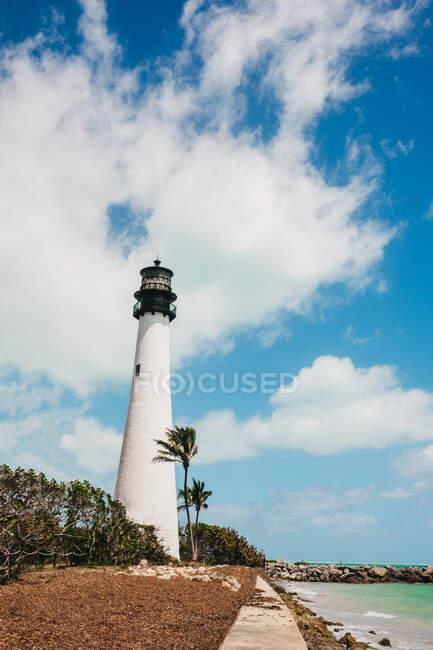 Vista del faro blanco parado en la orilla del mar en un día nublado en Miami - foto de stock