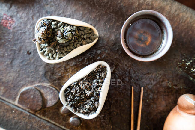From above teapot and dry tea leaves on oriental table for traditional ceremony — Stock Photo