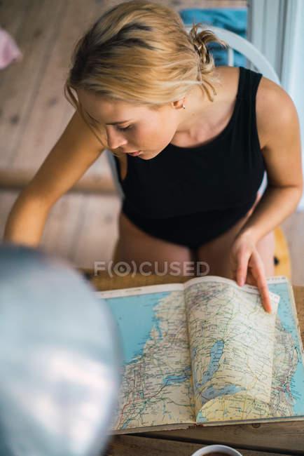 Молодая блондинка женщина, планирование поездки с картой — стоковое фото