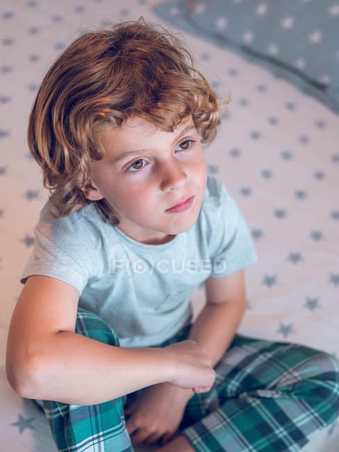 Очаровательный мальчик в пижаме сидит на удобной кровати и смотрит в сторону — стоковое фото