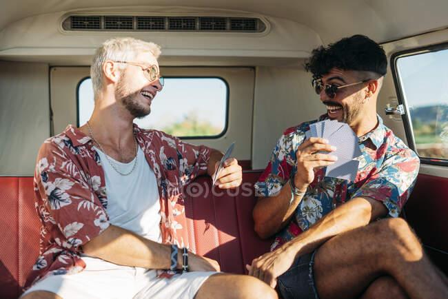 Веселі чоловіки грають у карти в фургоні. — стокове фото