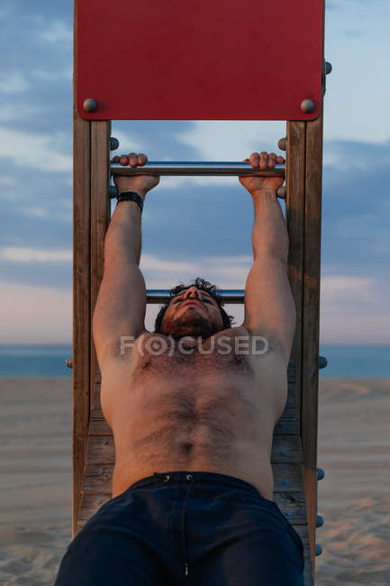 Shirtless muscular guy doing abdominal crunches on wooden slide on beach — Stock Photo