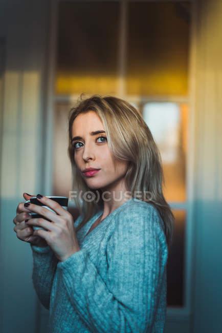 Donna bionda premurosa con coppa in piedi a casa — Foto stock