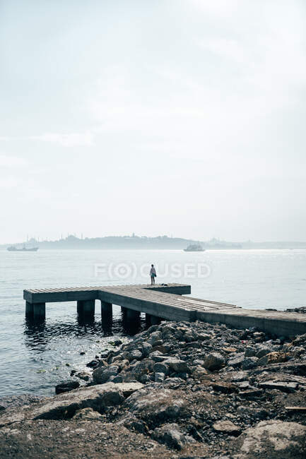 Back view of distant person standing on small pier and looking at sea in Istanbul — Stock Photo