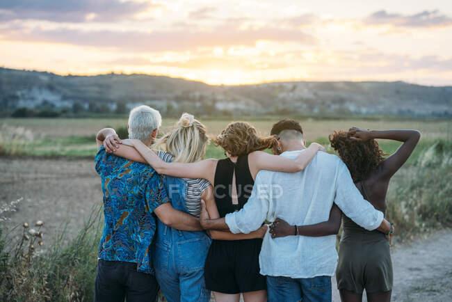 Rückansicht von jungen Männern und Frauen, die sich umarmen und den schönen Sonnenuntergang bewundern, während sie zusammen Zeit in der Natur verbringen — Stockfoto