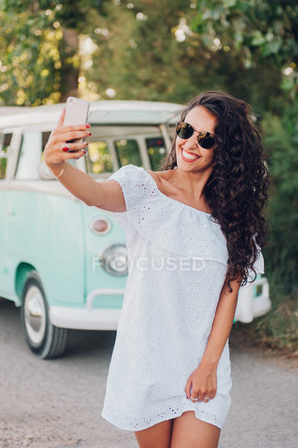 Cheerful young woman taking selfie in front of van in nature — Stock Photo