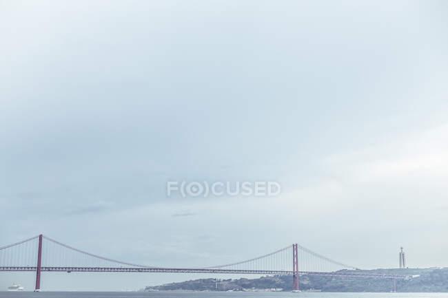 Пейзаж длинного подвесного моста над каналом воды в тумане под облачным небом, Синтра, Португалия — стоковое фото
