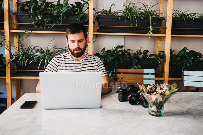 Casual bearded man with photo camera and smartphone sitting at table while using laptop — Stock Photo