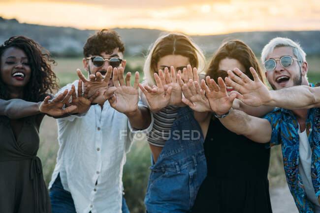 Gruppe verschiedener junger Freunde lächeln und reichen die Hände in Richtung Kamera, während sie vor dem verschwommenen Hintergrund einer atemberaubenden Landschaft während des Sonnenuntergangs stehen — Stockfoto