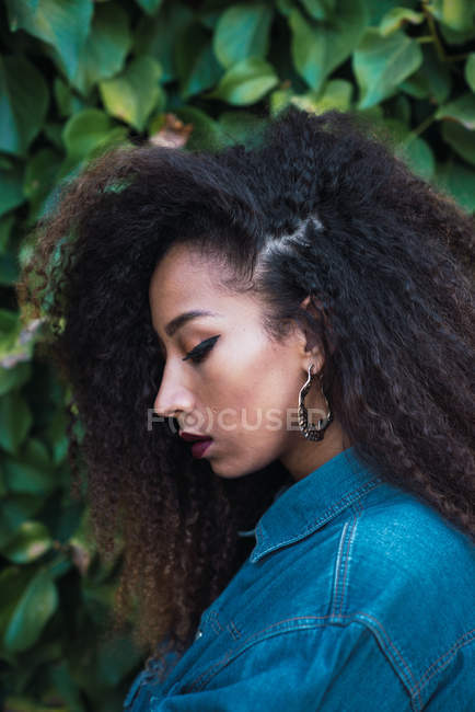 Pensativa mujer afroamericana de pie contra el arbusto verde - foto de stock