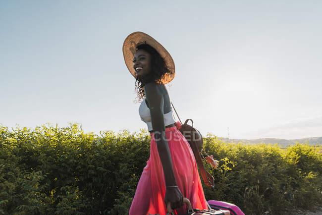 Trendige afroamerikanische Frau mit Hut und Koffer läuft im Sommer auf Landstraße — Stockfoto