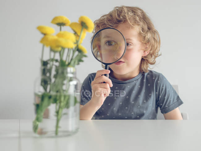 Curious little boy holding magnifying glass and looking through it on jar with pretty dandelions — Stock Photo