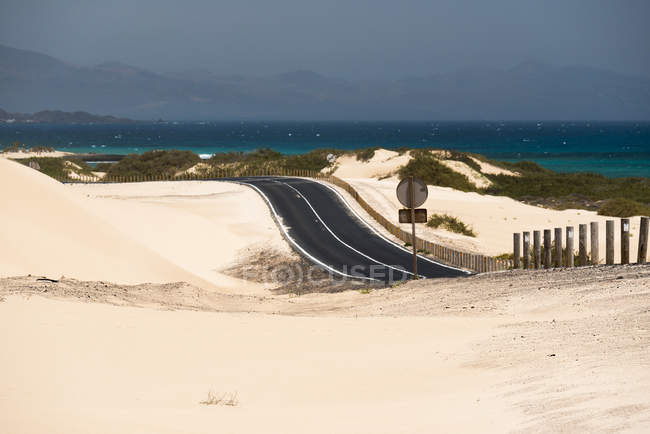 Road through desert and ocean water on Canary islands — Stockfoto