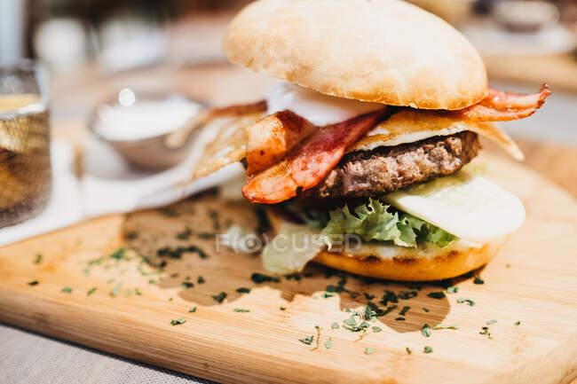 Von oben Nahaufnahme von köstlichen Burger serviert auf Holzbrett mit Eimer mit gebratenen Kartoffelkeilen und Sauce — Stockfoto