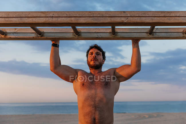 Bearded shirtless man climbing wooden ladder while exercising on beach — Stock Photo