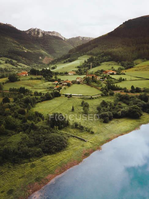 See und kleine Siedlung in grünen, malerischen Bergen — Stockfoto