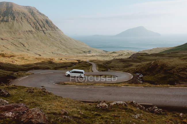 Auto bianca guida su strada serpentina in montagna sulle isole Feroe — Foto stock