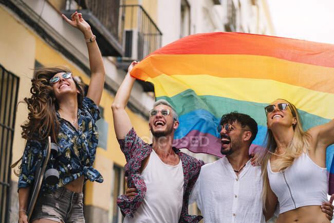 Группа друзей-геев с флагом гей-гордости на улице Мадрида — стоковое фото