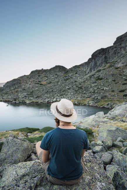 Jovem de chapéu sentado em rochas perto do lago e olhando para a vista — Fotografia de Stock