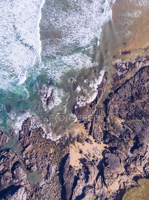 Vue imprenable sur les éclaboussures d'eau de mer près de longues falaises rocheuses par temps nuageux dans les Asturies, Espagne — Photo de stock