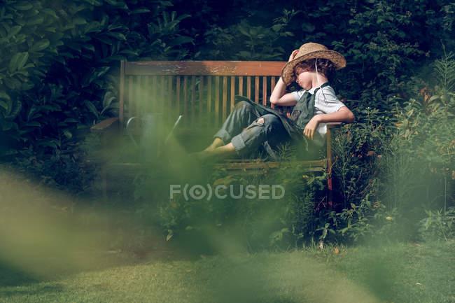 Мальчик в соломенной шляпе отдыхает на скамейке в саду — стоковое фото