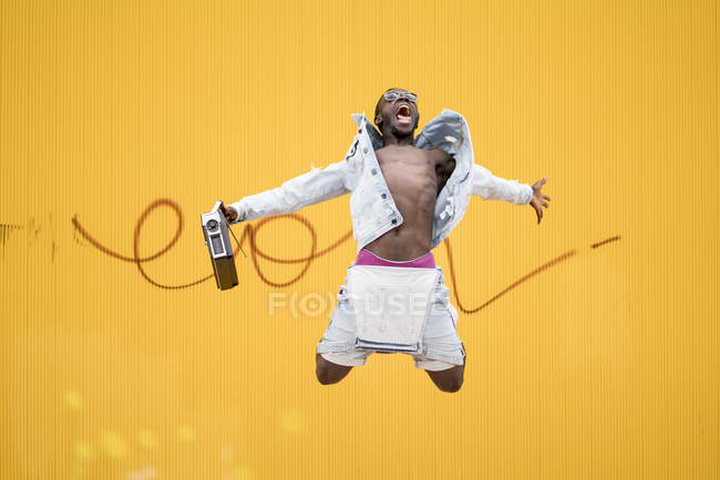 African american man jumping with vintage radio device on yellow background — Stock Photo