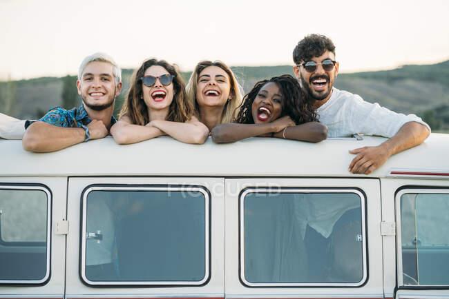 Группа разнообразных молодых друзей, стоящих в люке на крыше винтажного фургона и смотрящих в камеру, проводя время на природе вместе — стоковое фото