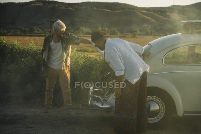 Los hombres frustrados cerca de un coche vintage roto - foto de stock