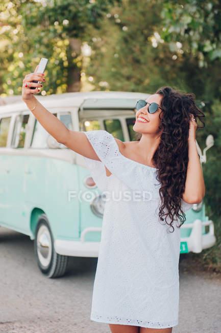 Jovem alegre tomando selfie na frente de van na natureza — Fotografia de Stock