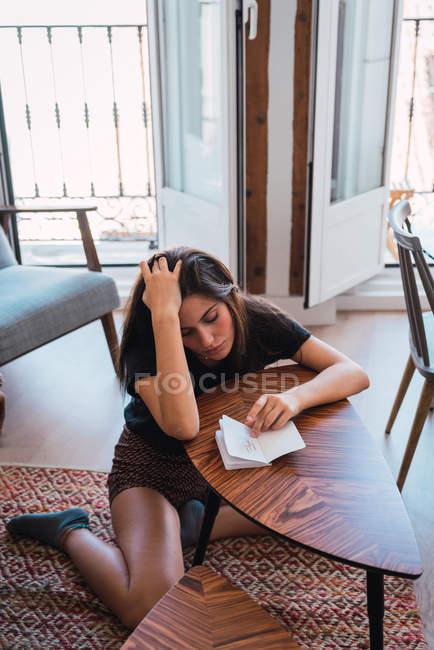 Jovem mulher pensativa sentada à mesa pequena de madeira no quarto e escrevendo no diário — Fotografia de Stock