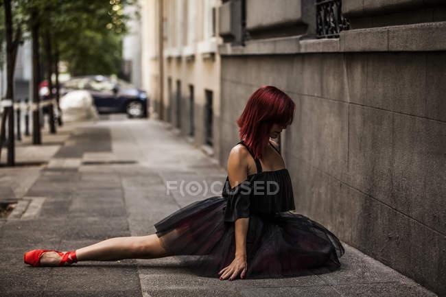 Рыжая балерина с черной пачкой и красными балетными кончиками, разогревающаяся, чтобы танцевать на улице, исполняющая позы — стоковое фото