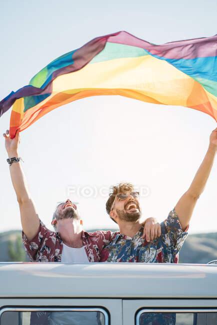 Двоє молодих чоловіків обіймають і тримають ЛГБТ-прапор над головами поки? стояв всередині ретро-фургона з відкритим дахом в природі. — стокове фото