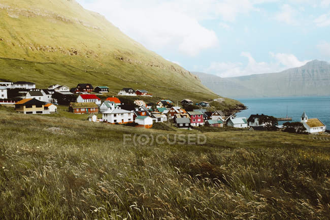 Vue sur petit village avec maisons colorées et montagnes verdoyantes sur les îles Feroe — Photo de stock