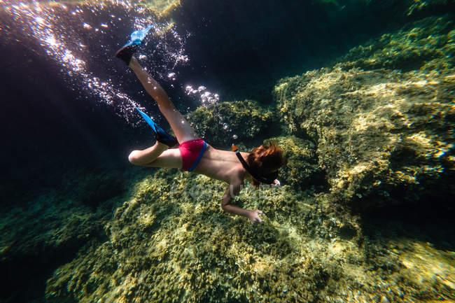 Unrecognizable boy diving in sea near rock — Stock Photo