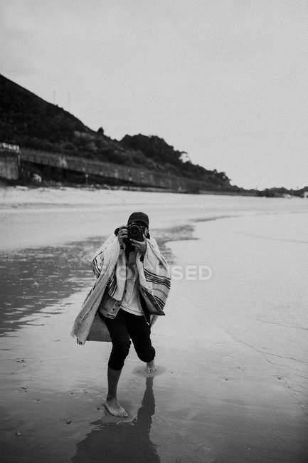 Pessoa andando na costa molhada e tirando foto — Fotografia de Stock