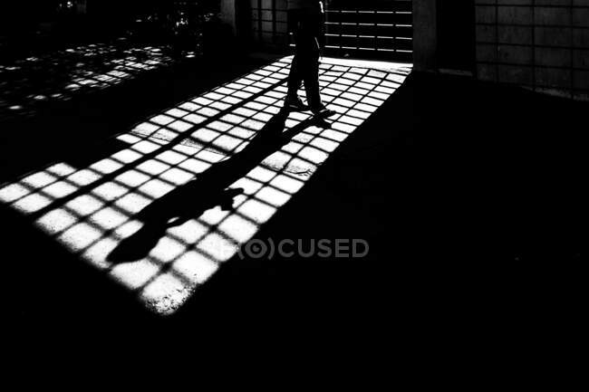 Silhouette of unrecognizable person walking at grid in locked room — Stock Photo