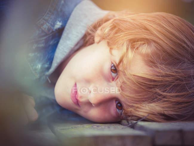 Biondo ragazzo sdraiato a bordo — Foto stock