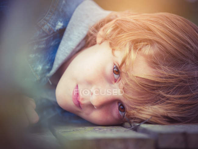 Blond boy lying on board — Stock Photo